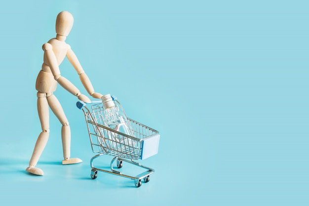 Buyer as wooden doll with grocery trolley with bottle of vodka on punchy blue.