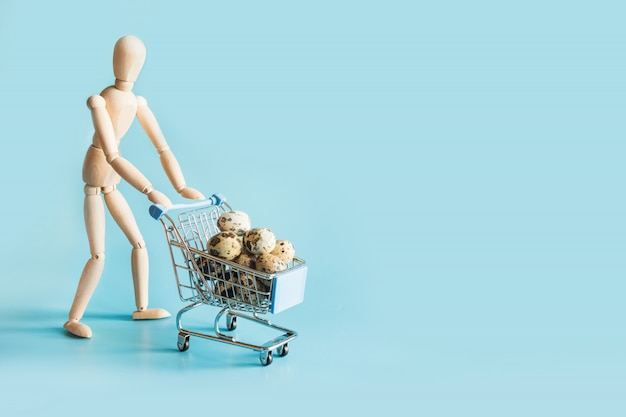 Buyer as wooden dolls with full grocery trolley of eggs.