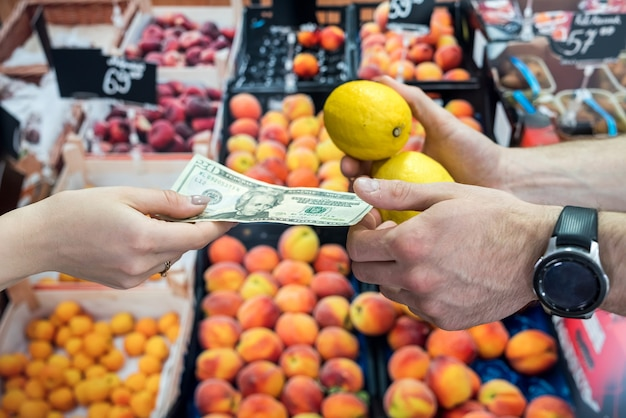 Покупатель дает деньги продавщице за фрукты в супермаркете. здоровый образ жизни