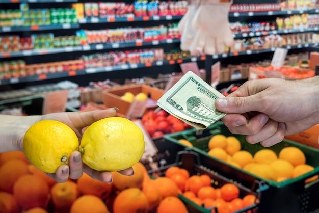 スーパーマーケットの果物のために店員にお金を与える買い手。健康的な生活様式
