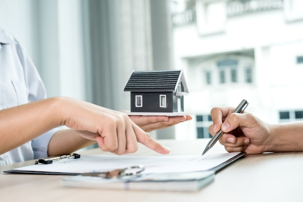 Buyer hand signs contract after real estate agents explains a business contract, lease, purchase, mortgage, loan, or home insurance.