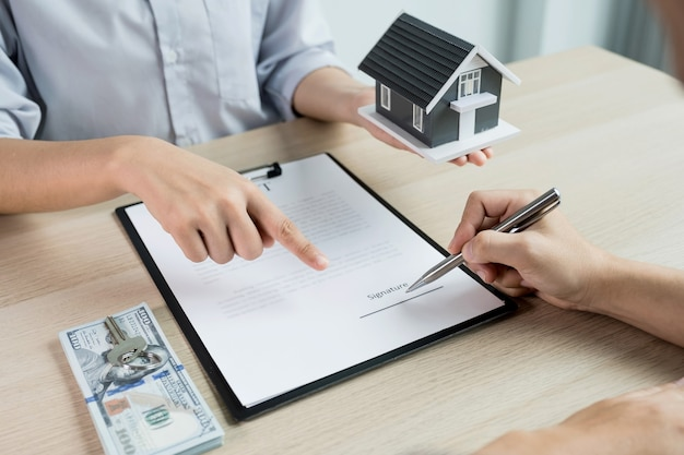 Buyer hand signs contract after real estate agents explains a business contract,