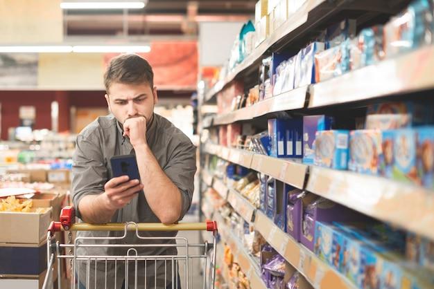 スーパーマーケットのバイヤーはスマートフォンを使用しています。食料品店の手でスマートフォンの男