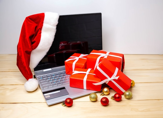 Buyer makes order on laptop, copy space on screen. woman buy presents, prepare to xmas, gift boxes and packages. purchasing things online. winter holidays sales. festive shopping with laptop