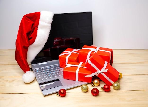 Покупатель делает заказ на ноутбуке, копируя место на экране. женщина покупает подарки, готовится к рождеству, подарочные коробки и пакеты. покупка вещей в интернете. распродажа зимних праздников. праздничный шоппинг с ноутбуком