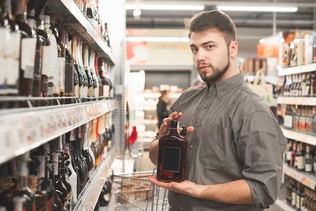 Мужчина-покупатель позирует перед камерой с бутылкой крепкого напитка в проходе супермаркета