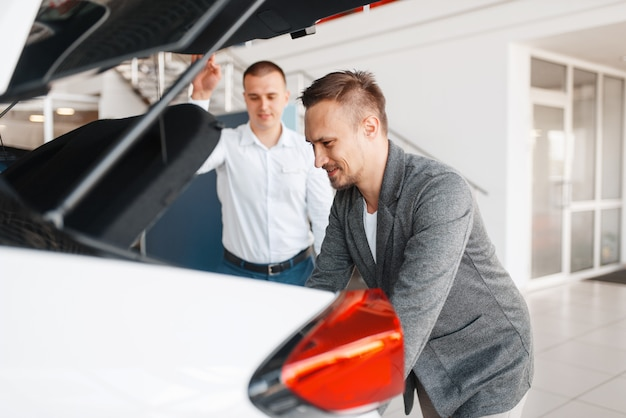 Buyer and manager looks at the trunk of new car in showroom. male customer choosing vehicle in dealership, automobile sale, auto purchase
