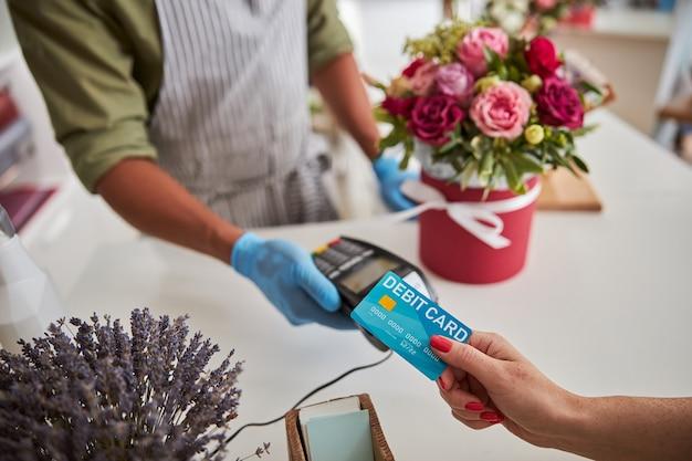 テーブルの上のポットに花束を入れながら、銀行カードをpos端末に置くバイヤー