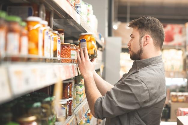 Покупатель выбирает консервы, покупает продукты в продуктовом магазине.