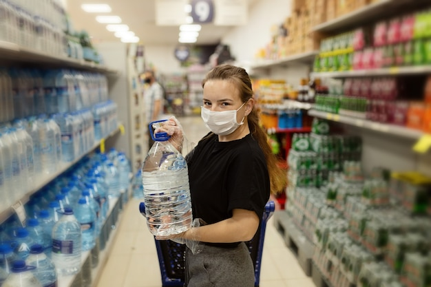 Покупатель в защитной маске. покупки во время пандемии. список срочных покупок. нехватка воды. панические покупки во время вспышки коронавируса. подготовка к пандемическому карантину.