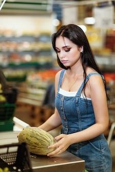 買い手はスーパーマーケットで電子はかりでメロンの重さを量ります