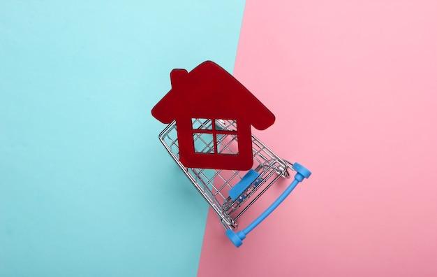 홈 컨셉 구매. 분홍색 파란색 배경에 집 그림으로 쇼핑 트롤리. 평면도