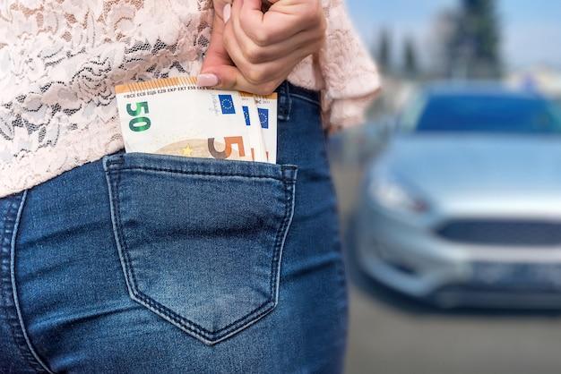 '자동차 구매'개념, 주머니에서 유로를 꺼내는 여자