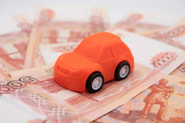 Buying a car in rubles toy car on the background of banknotes.