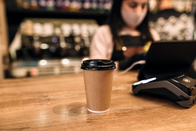 Buying a cup of coffee in a cafe, barista, nfc terminal