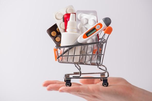 薬の概念を購入します。丸薬でいっぱいのプッシュカートと空のスペースで灰色の背景の上に分離されたデジタル温度計を示す広告を持っている女性の手の写真を閉じる