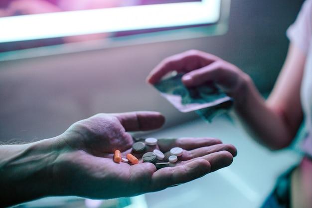 마약 구매. 마약 밀매 및 판매. 나이트 클럽에서 마약 딜러에서 마약을 구입하는 돈으로 마약 중독자의 손. 약물 남용 중지