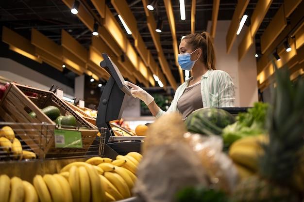 Покупка еды в супермаркете во время глобальной пандемии коронавируса