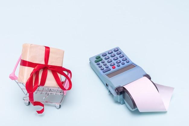 休日の概念のための贈り物を買う。オンラインショッピングのコンセプト。水色の背景に空白の白いチェックが付いたショッピングカートとレジのギフト。ビジネスコンセプト