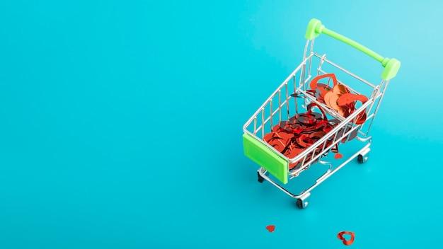 バレンタインデーのギフトを購入する、コピースペースのある緑の背景にスーパーマーケットからショッピングカートのトロリーでたくさんの心