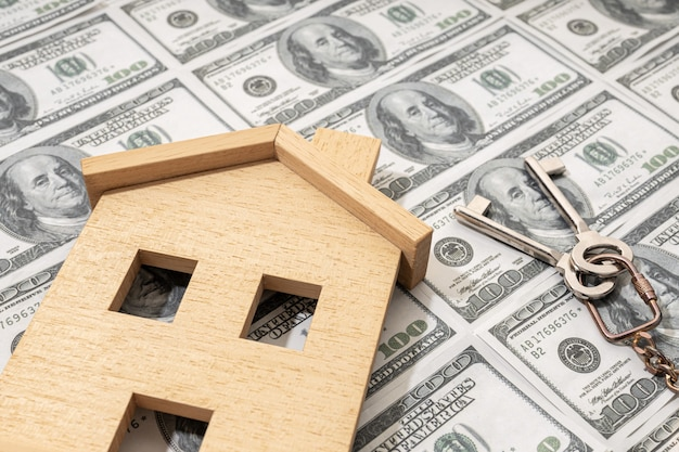 Buying a house or mortgage concept. real estate price. toy house on dollar banknote background