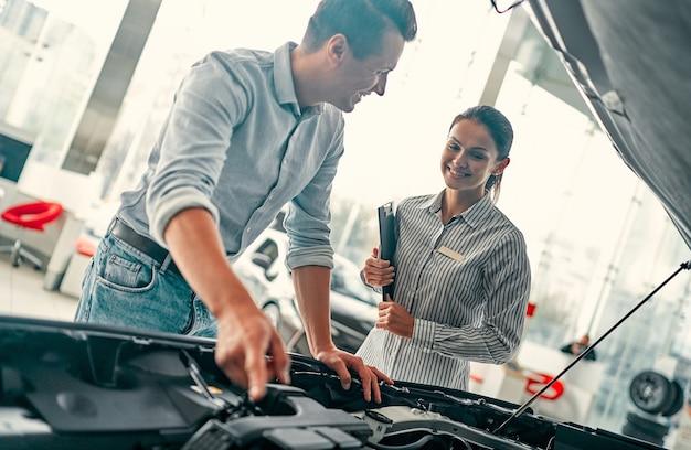 Покупка моей первой машины. молодая продавщица автомобилей стоит у автосалона и рассказывает красавцу об особенностях машины под капотом.