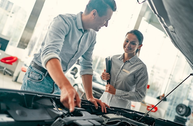 Buying my first car. young car saleswoman standing at the dealership telling about the features of the car under the hood to the handsome man.