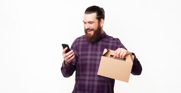 Покупая онлайн-ланч-бокс, веселый мужчина использует смартфон и держит ланч-бокс
