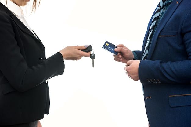 車の購入またはレンタル。クレジットカードとキーを保持している白で孤立したビジネスマン。
