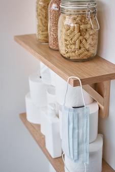 Покупка паники для домашнего карантина из-за коронавируса. оставайтесь дома для концепции защиты covid-19. запасы рулонов туалетной бумаги, защитной маски и продуктов на полке в домашних условиях