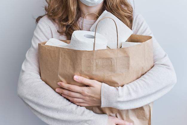 Покупка паники для домашнего карантина из-за коронавируса. оставайтесь дома для концепции защиты covid-19. женщина держит сумку с рулонами туалетной бумаги