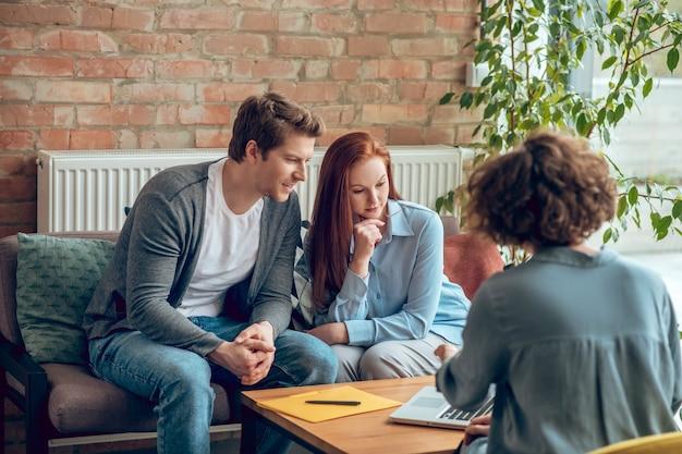 不動産の購入。不動産ブローカーと話している現代のオフィスのソファに座っている若い幸せなカップル