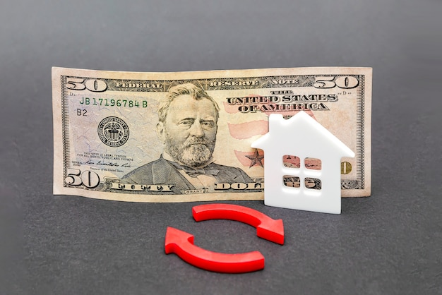 Buying real estate, buying a house. dollar banknote on a black background. real estate insurance concept, rental value, mortgage. copy space