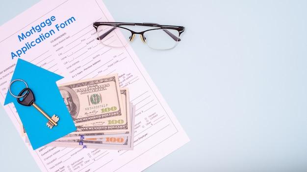 부동산 구매 개념. 새 아파트 또는 집에 대한 열쇠를 평평하게 놓으십시오 모기지 신청서의 100 달러 지폐, 계약의 명확성을 상징하는 안경, 복사 공간