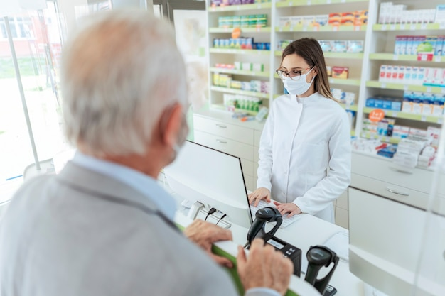 Buying and selling prescription drugs and pharmacist advice. an adult female pharmacist standing behind the counter and selling drugs to a mature man. she is wearing a protective mask