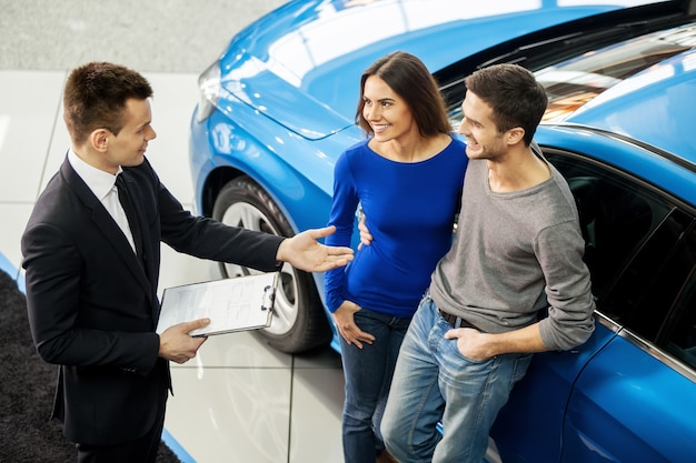 Buying their first car together. high angle view of young car salesman standing at the dealership telling about the features of the car to the customers