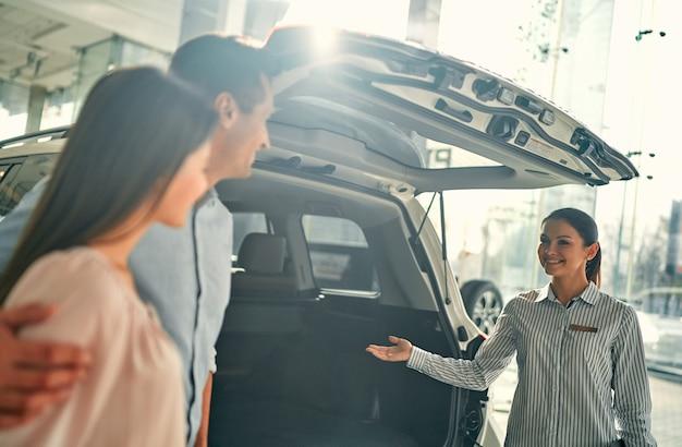 Вместе покупали свою первую машину. молодая продавщица автомобилей стоит у автосалона и рассказывает покупателям об особенностях автомобиля.
