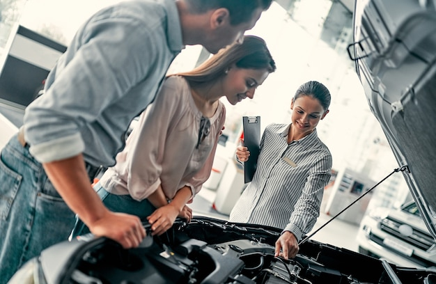 Buying their first car together. young car saleswoman standing at the dealership telling about the features of the car under the hood to the customers.