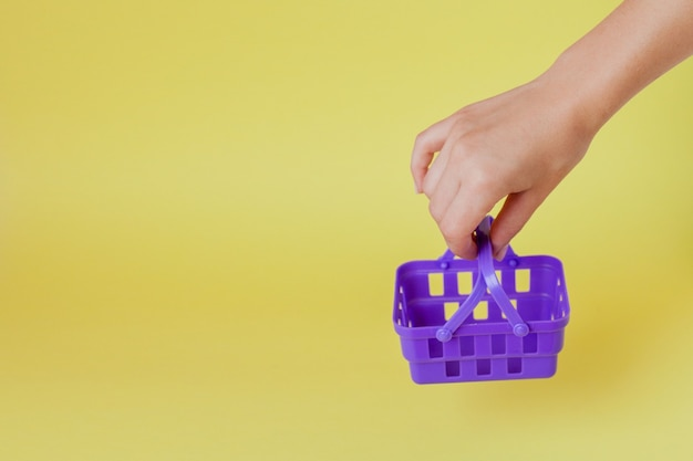 Buying things at market shops concept. woman hand holding small tiny shopping basket trolley over trend yellow background.