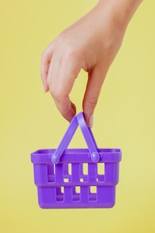 Buying things at market shops concept. woman hand holding small tiny shopping basket trolley over trend yellow wall.