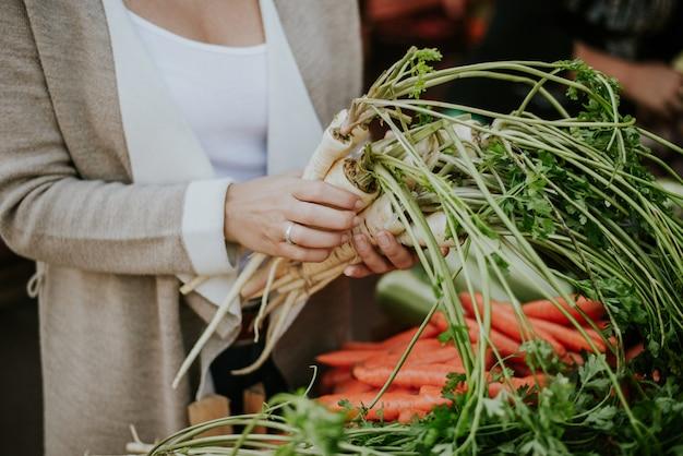 市場で野菜を買う。手のクローズアップで野菜。