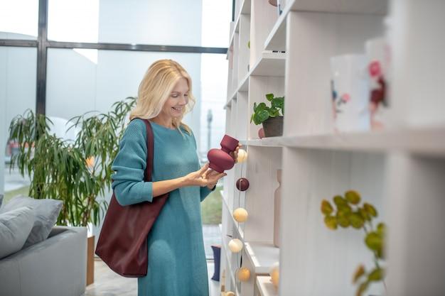 小さな赤い花瓶を手に持った棚の近くに立っているニットのドレスを着たbwomanは、彼女の喜びを見ていた。