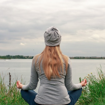 長い髪の美しい少女は、海岸に座っています。後ろからの眺め。日没。平和と静けさ。湖byのヨガ