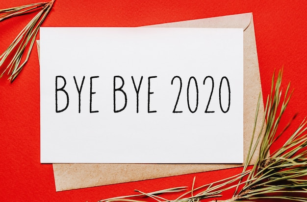 Bye bye 2020 christmas note with fir branch on red isolated background. new year concept
