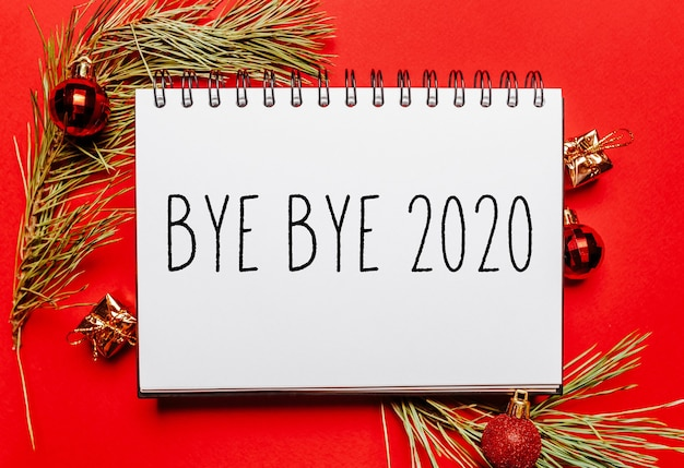 Bye bye 2020 christmas note with fir branch and toy on red