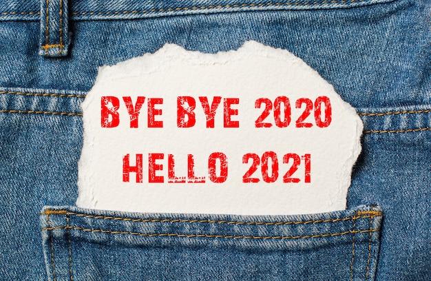 До свидания 2020, привет 2021 на белой бумаге в кармане джинсов