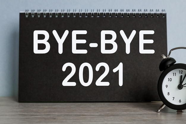 До свидания 2021 будильник, черный блокнот с текстом, на синем фоне, время убегает.