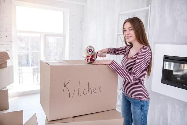 さようなら古い家。台所用品で箱を閉じながら笑顔とカメラとポーズをとる美しい黒髪の女性