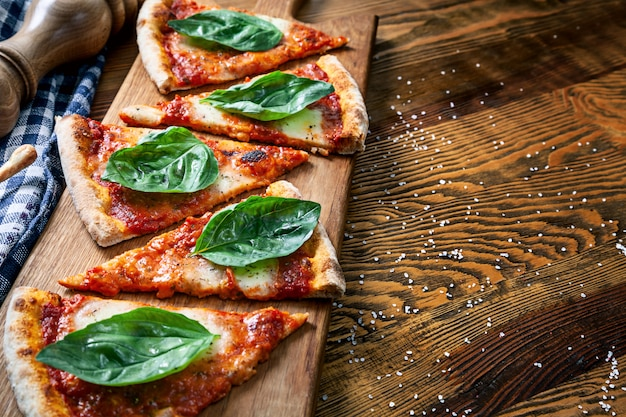 C;ose up view on sliced margarita pizza on wooden cutting board background. cutted pizza with copy space for design. picture for menu, italian cuisine