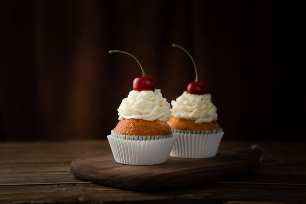 C shloseupot of delicious cupcakes with cream and cherries on top